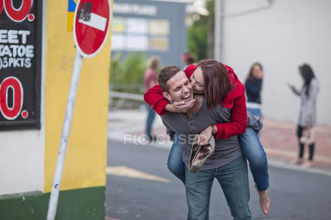 Homme adulte moyen donnant le ferroutage à la petite amie sur la rue de ville — Photo de stock