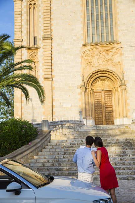 Vista posteriore della giovane coppia con convertibile guardando la mappa, Calvia, Maiorca, Spagna — Foto stock