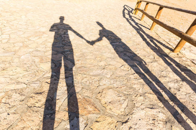 Shadows of two people holding hands at beach 923929bed6