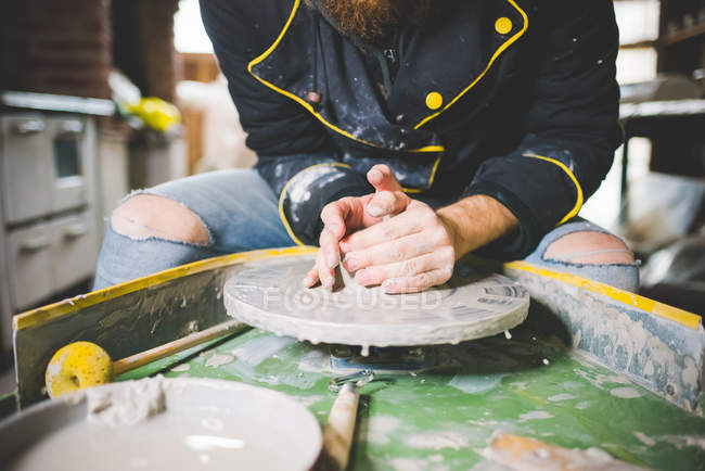 Cropped front view of mid adult man shaping clay on pottery wheel — Stock Photo
