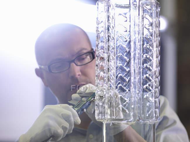 Travailleur effectuant un contrôle de qualité dans une usine de verre — Photo de stock