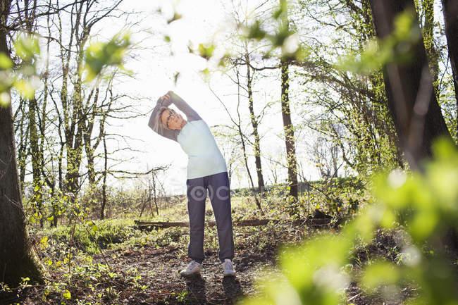 Donna in braccia foresta sollevata piegandosi lateralmente allungamento — Foto stock