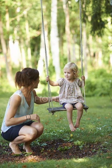 Mitte Erwachsene Mutter und Kleinkind Tochter spielen auf gartenschaukel — Stockfoto