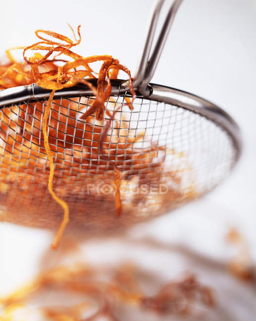 Deep fried carrot slices in sieve, close up shot — Stock Photo