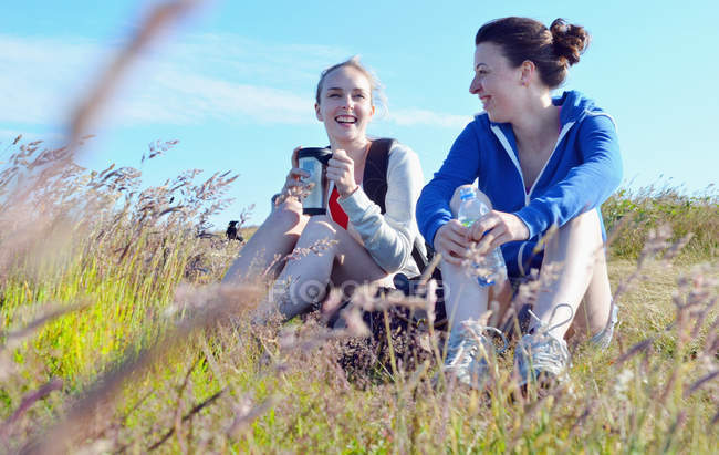 Two young women sitting on grass, drinking and talking — Stock Photo