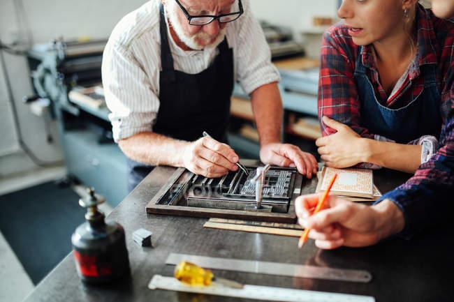 Старший ремесленник с помощью оборудования для печати и обучения молодых ремесленников и ремесленниц в типографии — стоковое фото