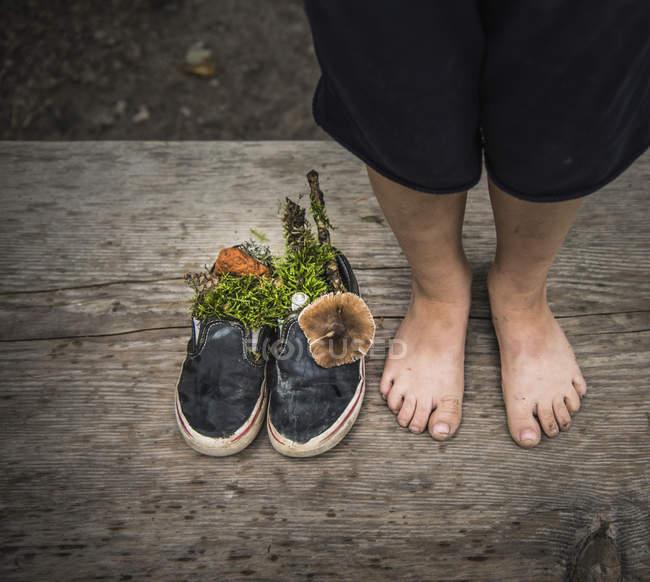 Nackte Füße von jungen neben Schuhen gefüllt mit der Natur — Stockfoto