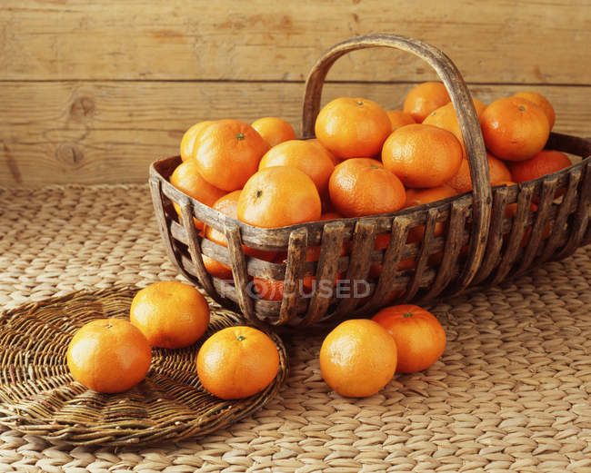 Vintage basket filled with tangerines on cloth — Stock Photo