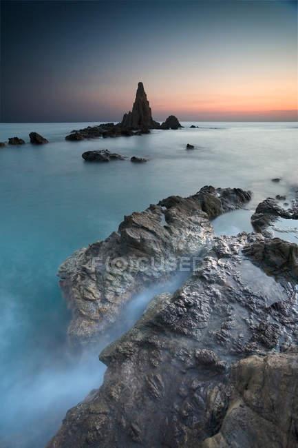 Nebbia rotolamento sulla spiaggia rocciosa — Foto stock