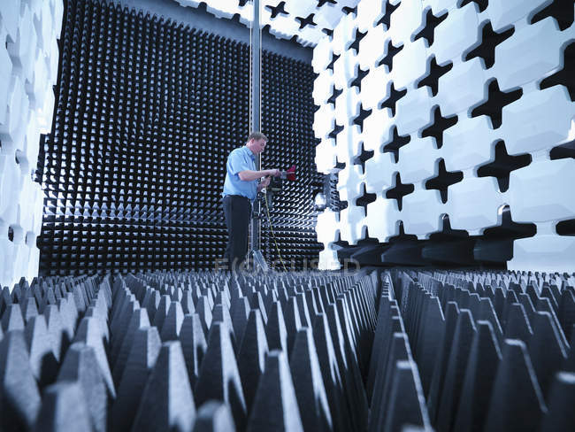 Engineer in anechoic chamber with horn antenna set up for Electromagnetic compatibility (EMC) radiated emission testing — Stock Photo