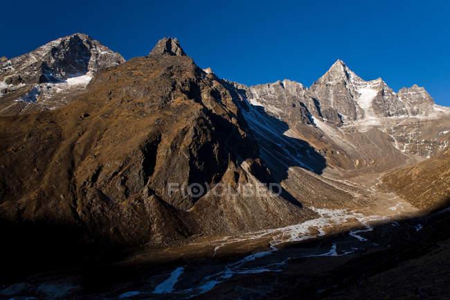 Snowcapped Скелясті гори і долини при яскравому сонячному світлі — стокове фото