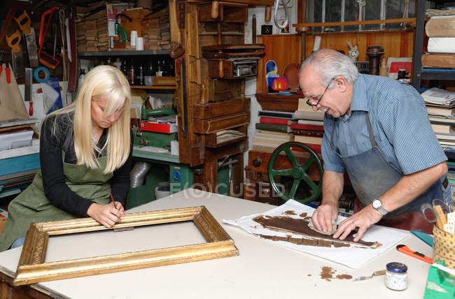 Старший чоловік і молода жінка, відновлюючи малюнок кадру та книги хребта в традиційних палітурне майстерні — стокове фото