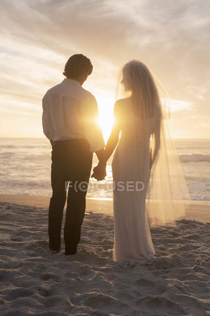 Bride and groom holding hands on beach against sunset — Stock Photo