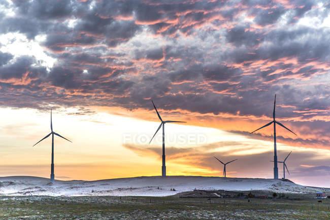 Éoliennes avec ciel coucher de soleil nuageux — Photo de stock