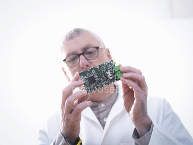 Engineer inspecting electronic circuitry for automotive use — Stock Photo