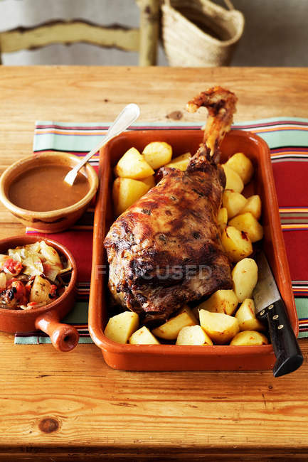 Baked lamb leg with roast potatoes and vegetables — Stock Photo
