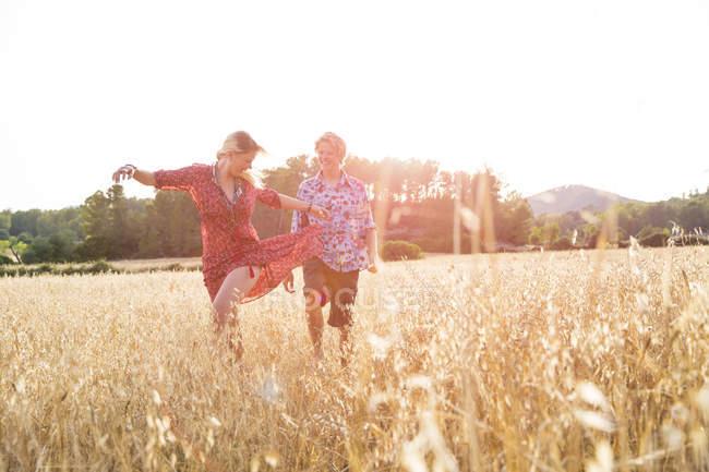 Giovane donna con fidanzato che balla nel campo di grano, Maiorca, Spagna — Foto stock