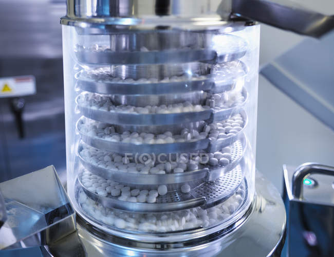 Close up of tablets in tablet pressing machine in pharmaceutical factory — Stock Photo