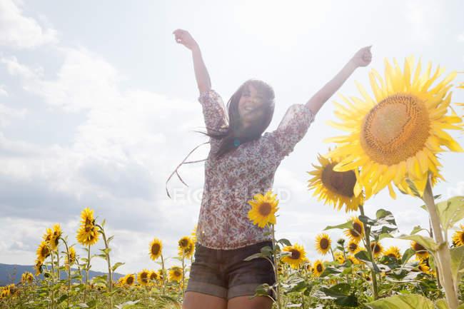 Femme adulte moyenne dans le champ de tournesols — Photo de stock