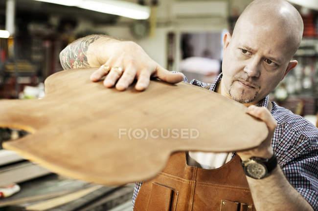 Guitar maker checking wooden guitar shape in workshop — Stock Photo