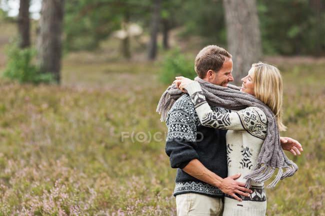 Couple adulte moyen enveloppé dans un foulard étreignant — Photo de stock