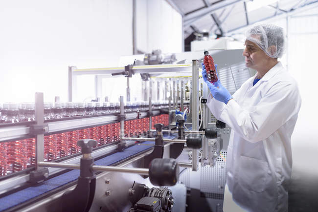Рабочий осматривает бутылку воды на производственной линии на заводе родниковой воды — стоковое фото