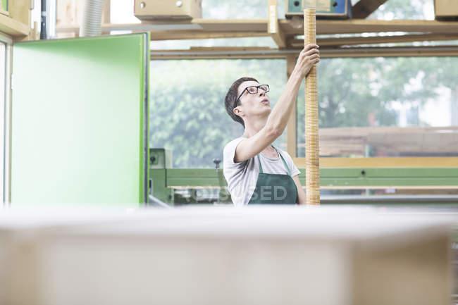 Woman in workshop holding alphorn — Stock Photo