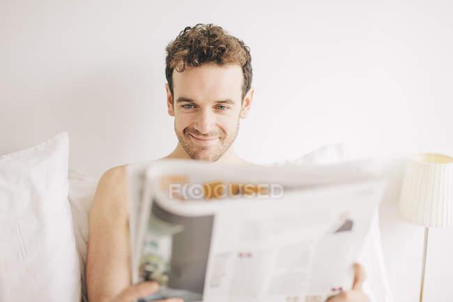 Junger Mann im Bett schmunzelnd beim Zeitung lesen — Stockfoto