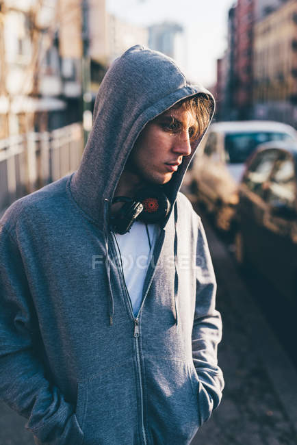 Man wearing hooded top and headphones, hands in pockets looking away — Stock Photo