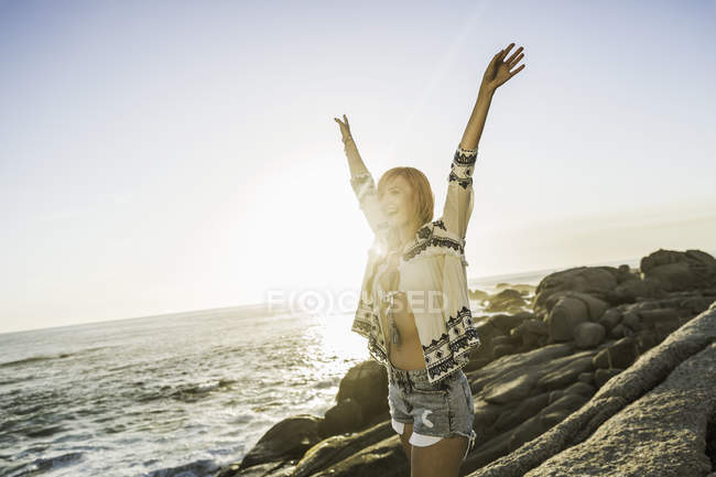 Mujer adulta media en Playa soleada con los brazos alzados, ciudad del cabo, Sudáfrica - foto de stock