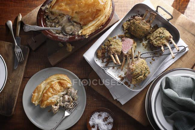 Prato de torta de frango com porção e racks de cordeiro assado na mesa — Fotografia de Stock