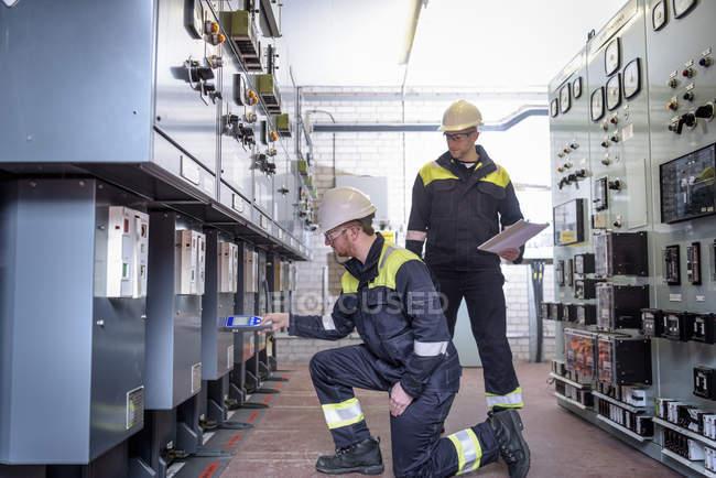 Essais des travailleurs pour détecter le bruit dans la sous-station électrique — Photo de stock