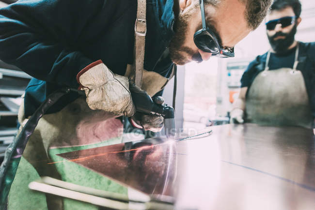 Metalworker plasma-cutting copper sheet in forge workshop — Stock Photo