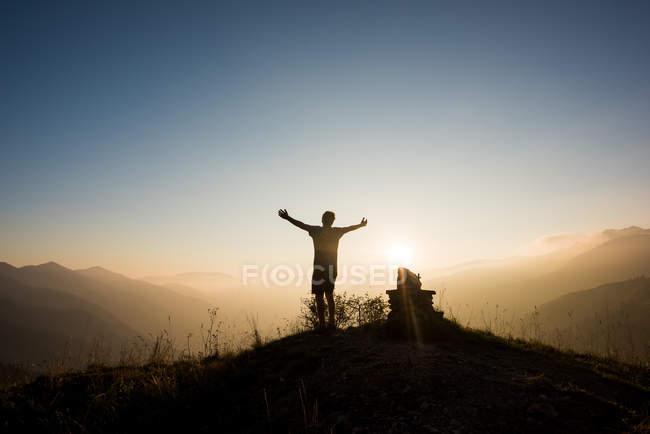 Rear view of man on mountain peak, arms raised, Passo Maniva, Italy — Stock Photo