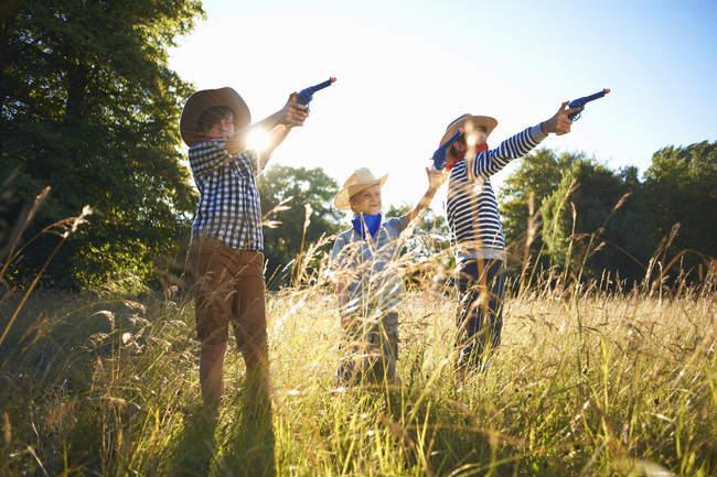 Three little boys dressed as cowboys holding toy guns — Stock Photo