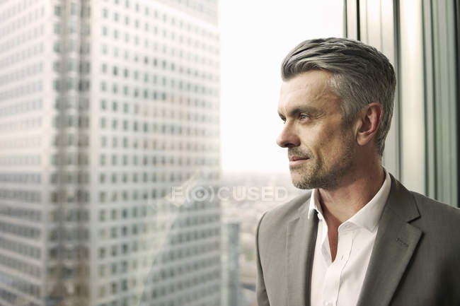 Портрет зрелого бизнесмена, смотрящего из окна офиса — стоковое фото