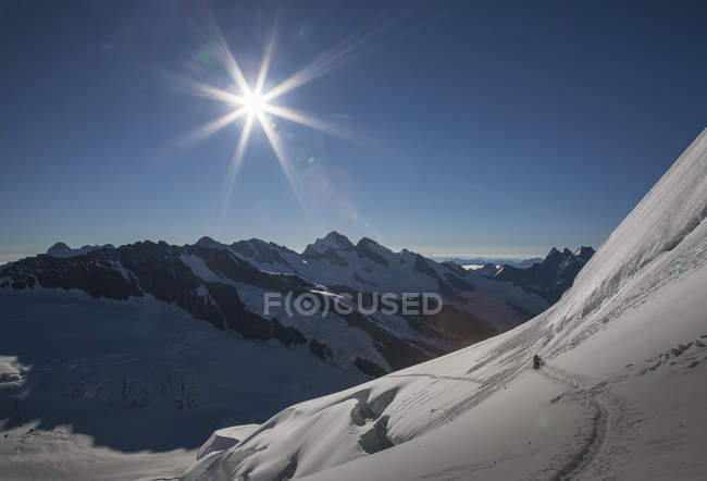 Nieve cubre el paisaje de montaña con excursionistas distantes - foto de stock