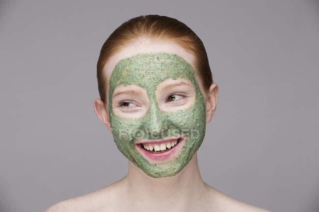 Junge Frau mit Gesichtsmaske, lächelnd — Stockfoto