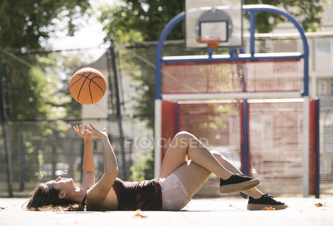 Young woman lying on basketball court throwing ball — Stock Photo