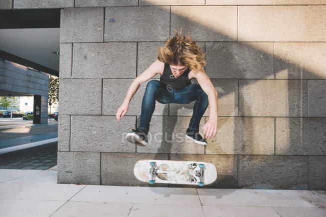 Junge männliche urban Skater tun oben Skateboard Skateboard Sprung-trick — Stockfoto