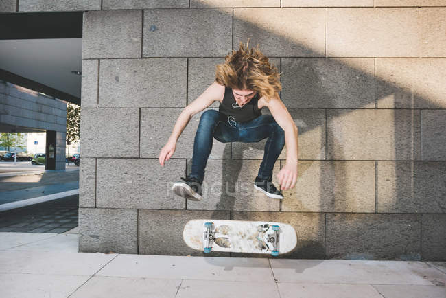 Jeune skateur urbain mâle faisant skateboard trick saut au-dessus de skateboard — Photo de stock
