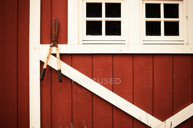 Shears hanging from red barn wall — Stock Photo
