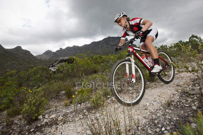 Jeune homme VTT descendant la montagne — Photo de stock