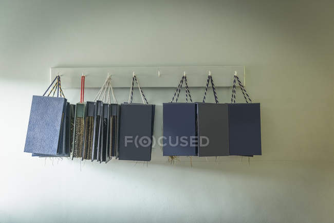 Material sample books hanging in clothing factory — Stock Photo