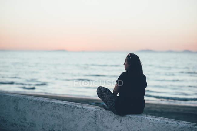 Vista posteriore della donna seduta sul muro guardando l'oceano, Sorso, Sassari, Italia — Foto stock