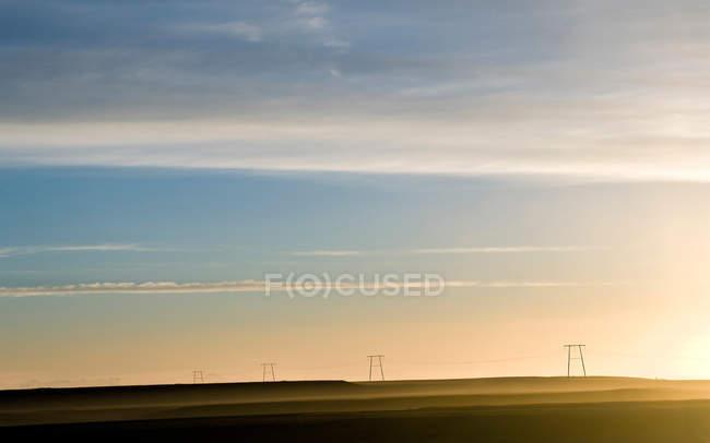 Grünes Feld mit Pylonen und Sonnenuntergang Wolkengebilde — Stockfoto