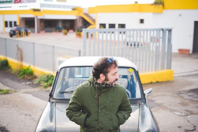 Средний взрослый мужчина, опираясь на старинных автомобилей, глядя через плечо — стоковое фото