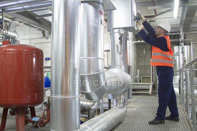 Техник пытается проверить трубы на электростанции — стоковое фото