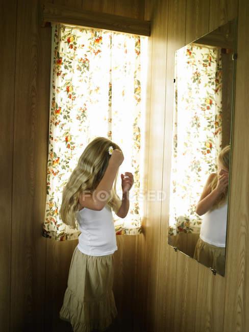 Garota penteando o cabelo loiro comprido no espelho do quarto — Fotografia de Stock