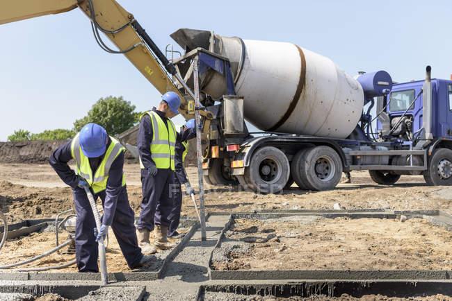 Apprentis constructeurs posant des fondations en béton sur le chantier — Photo de stock